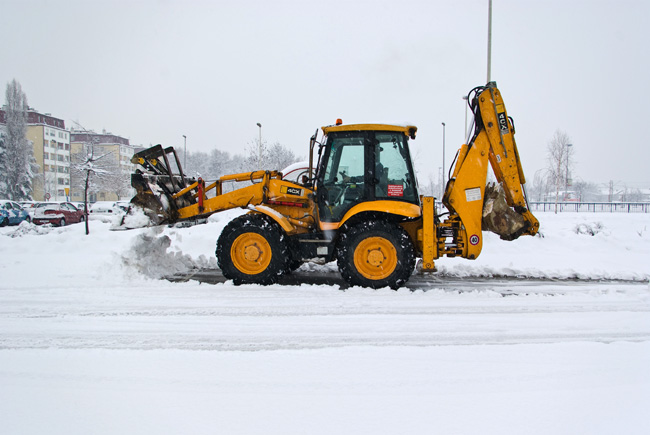snow plow clearing parking lot